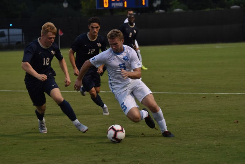 Center defender John Nelson (5) fights for the ball against midfielder Tim Townsend (18) during Saturday night's game against Pittsburgh at Koskinen Stadium.