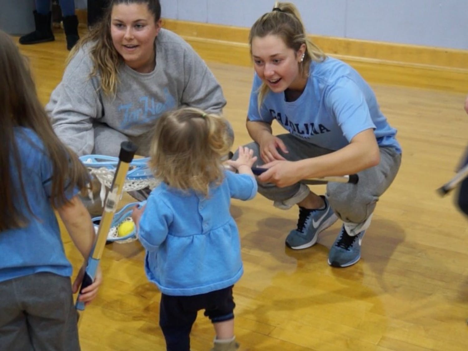 Jamie Ortega (right) and Kate Kotowski of UNC Women's Lacrosse talk to a young participant during National Girls and Women in Sports Day, hosted at UNC.