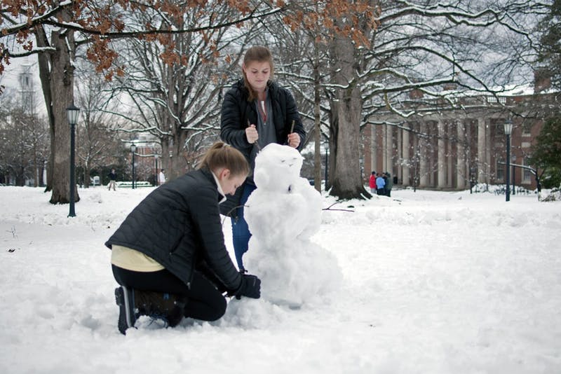Freshmen Grace Baldridge and Emily Imes make a snowman on the quad on Thursday.
