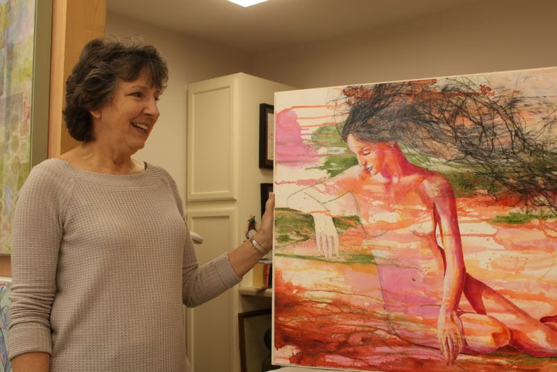 "Visual artist Nancy Smith stands by her painting ""From the Depths of the Earth"" in her home studio on Saturday, March 2, 2019. Nancy's paintings, which were created using acrylic and mixed media, are being hosted by the FRANK gallery."