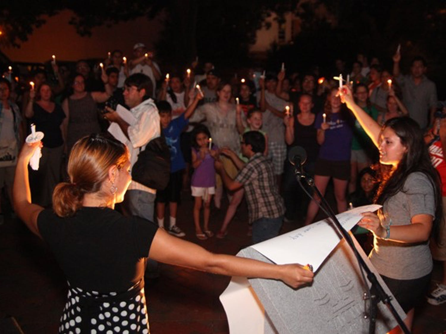 """Rosario Lopez (left) and Viridiana Martinez lead community members in singing """"We Shall Overcome"""" on Tuesday night in Raleigh. Lopez and Martinez, who are both undocumented immigrants, had just ended their 14-day hunger strike, which was raising support for the DREAM Act."""