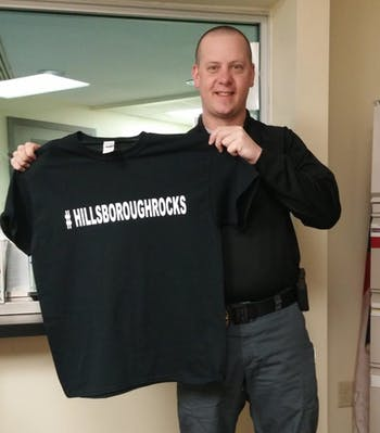 "Hillsborough Lt. Andy Simmons holds up a t-shirt with the slogan ""#HillsborouhgRocks"" on it. Photo Courtesy of Lt. Andy Simmons."