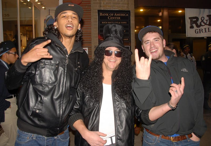 "Brian Gourly, center, of Oxford, N.C., poses as Guns 'n Roses guitarist Slash. ""There has been a lot of horns and whistling and a lot of yelling,"" Gourly said."