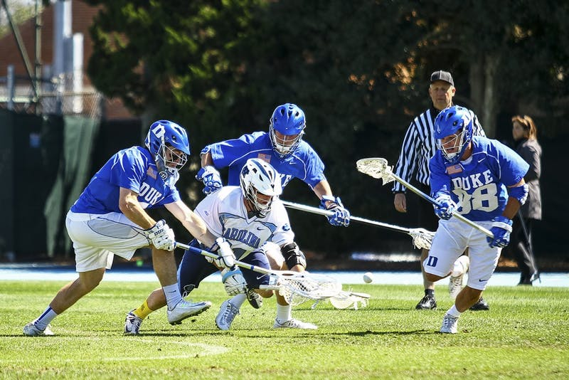 UNC senior attackman Joey Sankey (11) fights for the ball.