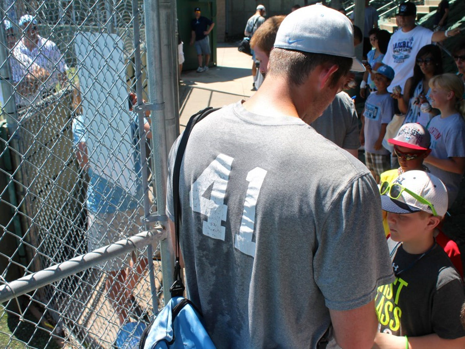 Kent Emanuel signs autographs for waiting fans after Monday afternoon's practice.