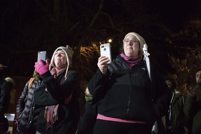 Two demonstrators record organizers speaking to the crowd at a gathering to celebrate the removal of Silent Sam's pedestal and plaques in the Peace and Justice Plaza on Tuesday, Jan. 15, 2019.