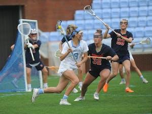 Women's lacrosse junior Katie Hoeg runs past multiple defenders during a game against Syracuse on April 13, 2019. UNC beat Syracuse 11-5.
