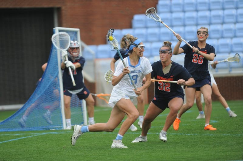 Women's lacrosse junior Katie Hoeg runs past multiple defenders during a game against Syracuse on April 13, 2019. UNC beat Syracuse 11-5.