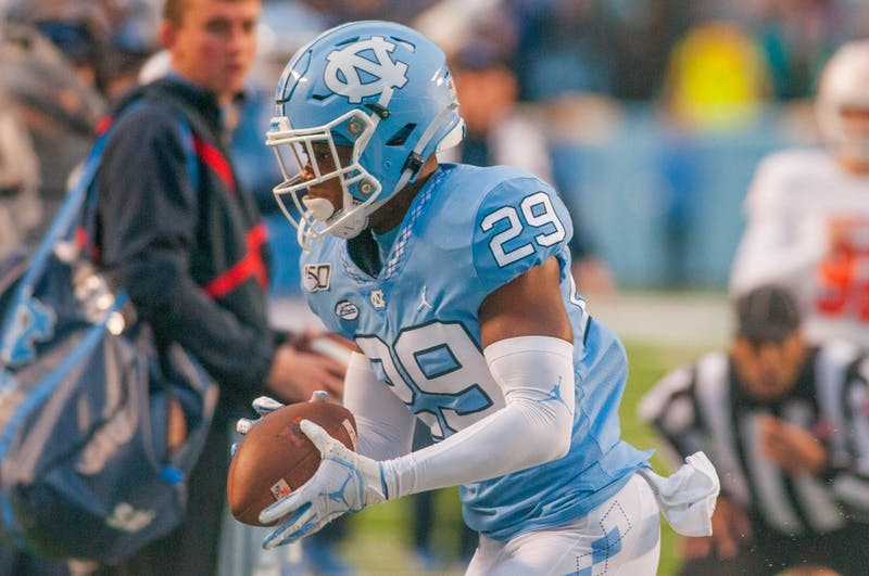 UNC freshman defensive back Storm Duck (29) runs the ball to the sideline. The Tar Heels beat the Bears 56-7 at Kenan Memorial Stadium on Saturday, Nov. 23, 2019.