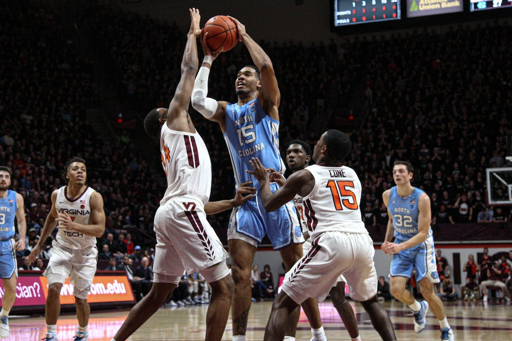 Junior forward Garrison Brooks (15) fights for the shot against Virginia Tech's P.J. Horne (14) and Jalen Cone (15) on Wednesday, Jan. 22, 2020 in Cassell Coliseum. UNC fell to Virginia Tech 79-77.