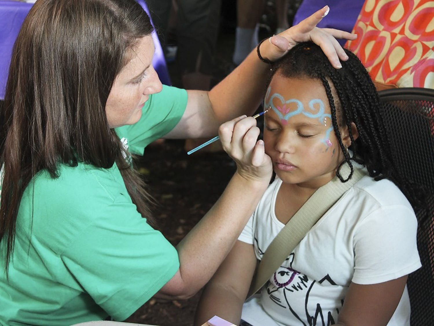 Laila Williams, eight years old, gets her face painted at the Weaver Street Co-Op Fair in Carborro.