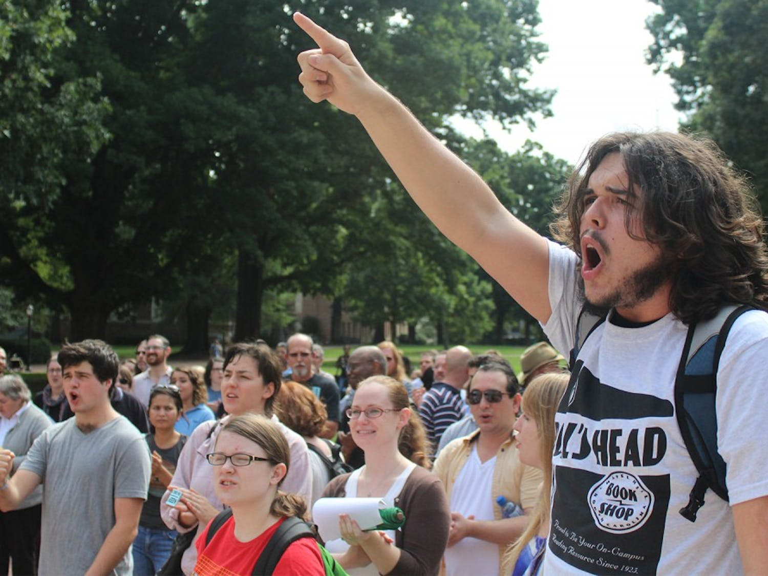 Students and staff protest the possible privatization of the UNC Student Stores: Freshman Tristan Bavol (linguistics major) (right) helps lead demonstrators in front of the South Building