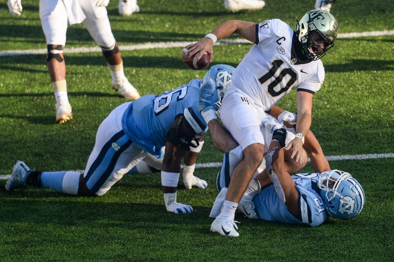 Wake Forest's redshirt sophomore quarterback Sam Hartman (10) is sacked by UNC's graduate linebacker Chazz Surratt (21) and sophomore defensive lineman Tomari Fox (56) during a game in Kenan Memorial Stadium during a game on Saturday, Nov. 14, 2020. UNC beat Wake Forest 59-53.