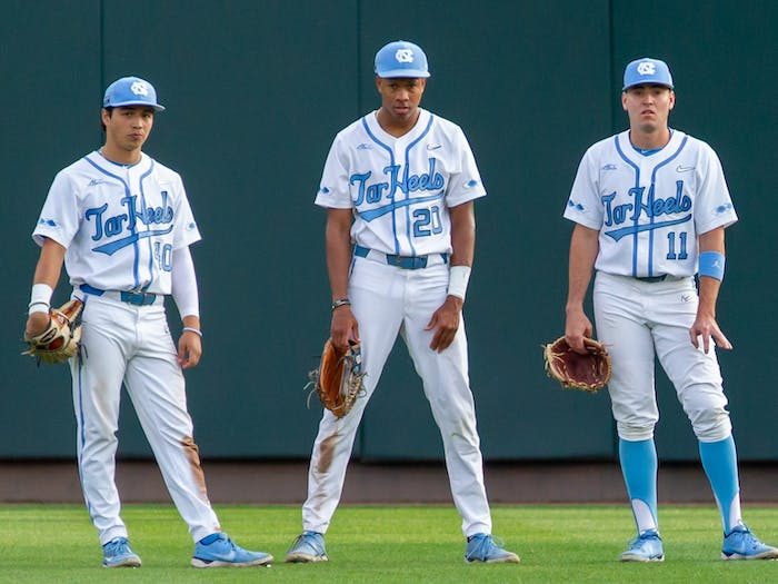 UNC outfielders Angel Zarate (10), Justice Thompson (20), and Caleb Roberts (11) wait in the outfield during a timeout at the game against UNCW on Tuesday May 18, 2021 at Boshamer stadium. The Tar Heels won 14-9.