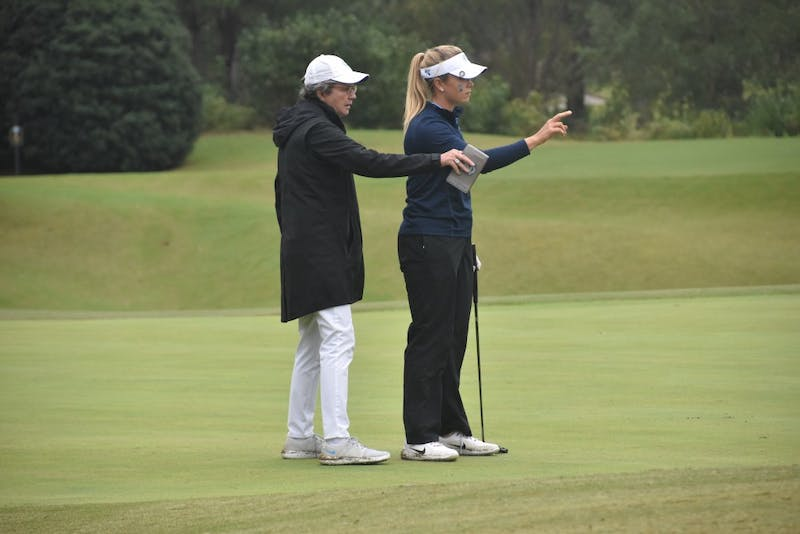 UNC junior Kelly Whaley and UNC women's golf head coach Jan Mann line up a putt during the Tar Heel Invitational tournament on Sunday, Oct. 14, 2018.