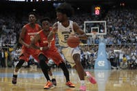 First year guard Coby White dribbles past a Syracuse defender in the Smith Center on Tuesday Feb. 26, 2019. UNC beat Syracuse