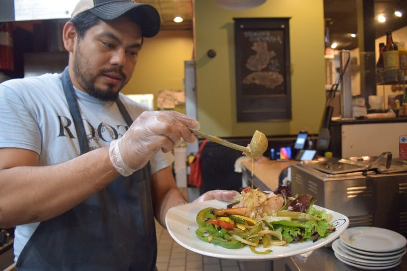 Gabriel Ordoñez, one of the owners of Roots Bistro & Bar, makes a salad on Friday, Sept. 21. Originally form Guatemala, Ordoñez has been able to expand to a second location in Durham and says that there is a lot of competition on Franklin St., making business harder at the Chapel Hill location.