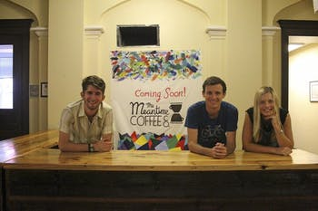 Scott Diekema (left), Keegan McBride and Lauren Eaves pose in front of the new sign for Meantime Coffee.