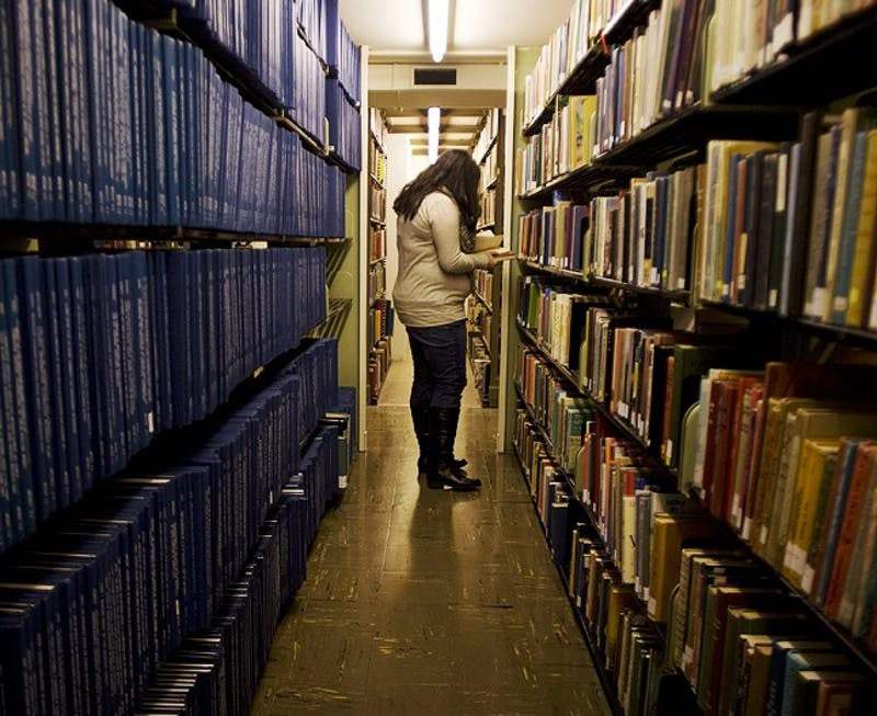 Junior Biology Major Dipa Desai sifts through books in the stacks in the SILS Library in Manning Hall. The School of Information and Library Science just announced that it is offering a 5-year masters program. SILS is the number one information and library science school in the country.