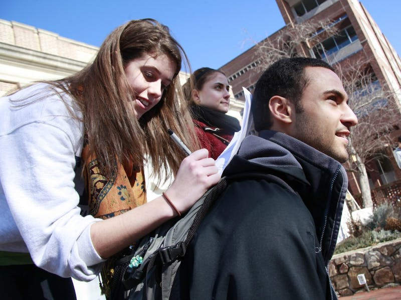 Hannah Sacco, junior at UNC-Chapel Hill, with the assistance of Mohammad Saad's back, fills out petitions for Student Body President and Senior Class Representatives on Jan. 19.