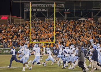 UNC players rush the field after Casey Barth's field goal puts the Tar Heels up 30-27 for the win.