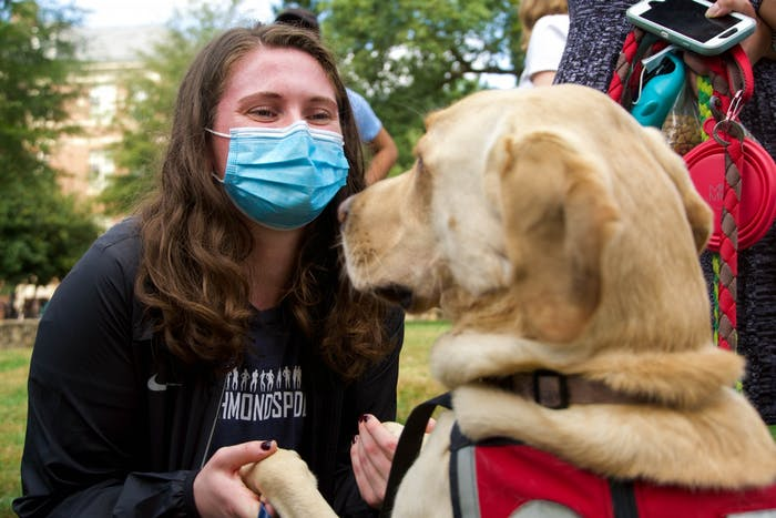 Content warning: The text below contains mention of suicide. Lauren McRae, a graduate student, plays with Hunter, a graduated service dog from Eyes Ears Nose and Paws. EENP is a non-profit organization that trains service dogs to partner with people who have disabilities. On Wednesday, they brought several dogs and volunteers to the quad to play with students and offer support as the campus community grapples with student deaths this semester.