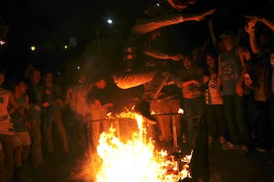 Students jump over bonfires set onFranklin Street after North Carolina's 76-72 victory over Dukeon Saturday.