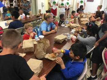 UNC women's soccer midfielder Megan Buckingham eats lunch with Food for the Summer attendees. Photo courtesy of the Town of Chapel Hill.