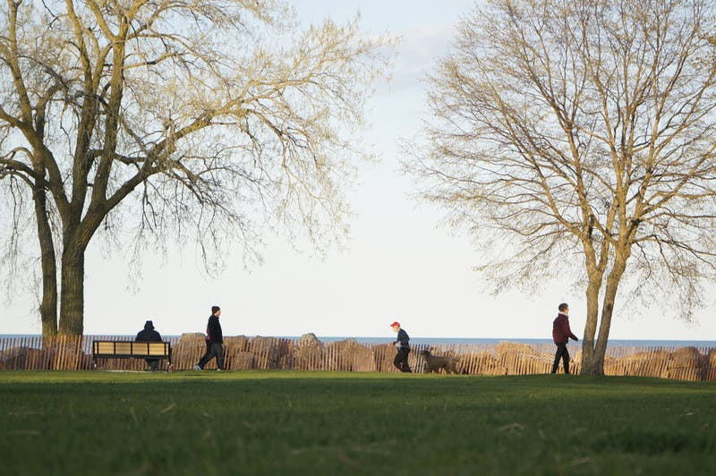 A man with a face mask runs his dog alongside Lake Michigan in Evanston, IL on Wednesday, May 6, 2020. Despite numerous public health announcements, none of the other members of the public are wearing facial masks or any other forms of personal protective equipment.