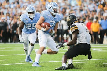 UNC freshman quarterback Sam Howell (7) rushes past Appalachian State senior defensive back Josh Thomas (7) during a game in Kenan Memorial Stadium on Saturday, Sept. 21, 2019. The Tar Heels lost to the Mountaineers 31-34 in their second consecutive loss.