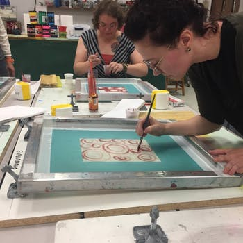 Participants engaging in a previous screen printing event at The Scrap Exchange. Photo courtesy of Robby Poore.