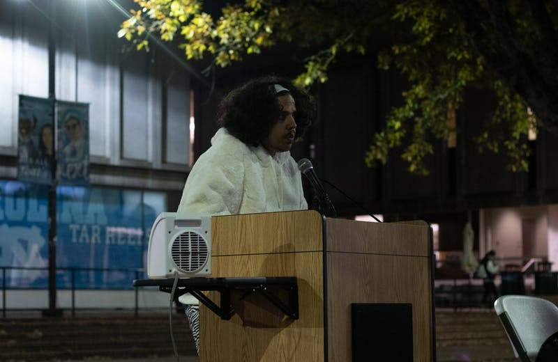 Poet Amir Rabiyah reads poems honoring trans people who have lost their lives in the past year. UNC LGBTQ Center held a candlelight vigil remembering the lives of trans people who died in the past year as part of Transgender Day of Remembrance at the Pit on Wednesday, Nov. 20, 2019.