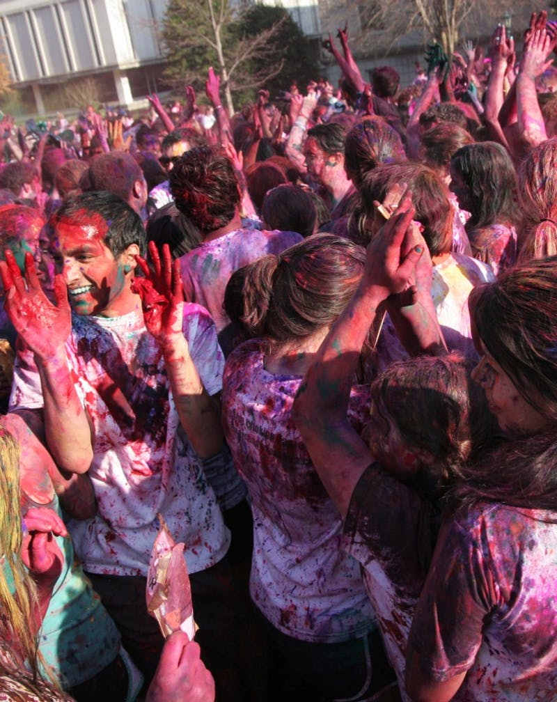 Students throw paint during UNC's Holi celebration Friday afternoon.