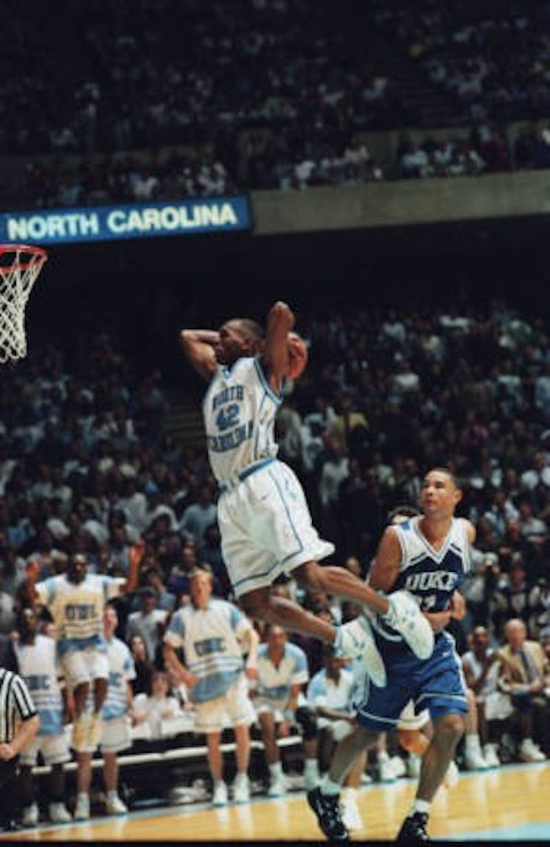 "Jerry Stackhouse (UNC #42) dunking at UNC-Chapel Hill versus Duke University basketball game at Dean Smith Center, Chapel Hill, NC; negatives labeled ""Jerry Stackhouse - print."" UNC v. Duke basketball, Jerry Stackhouse dunk, in the Hugh Morton Photographs and Films #P0081, copyright 1993-1995, North Carolina Collection, University of North Carolina at Chapel Hill Library."