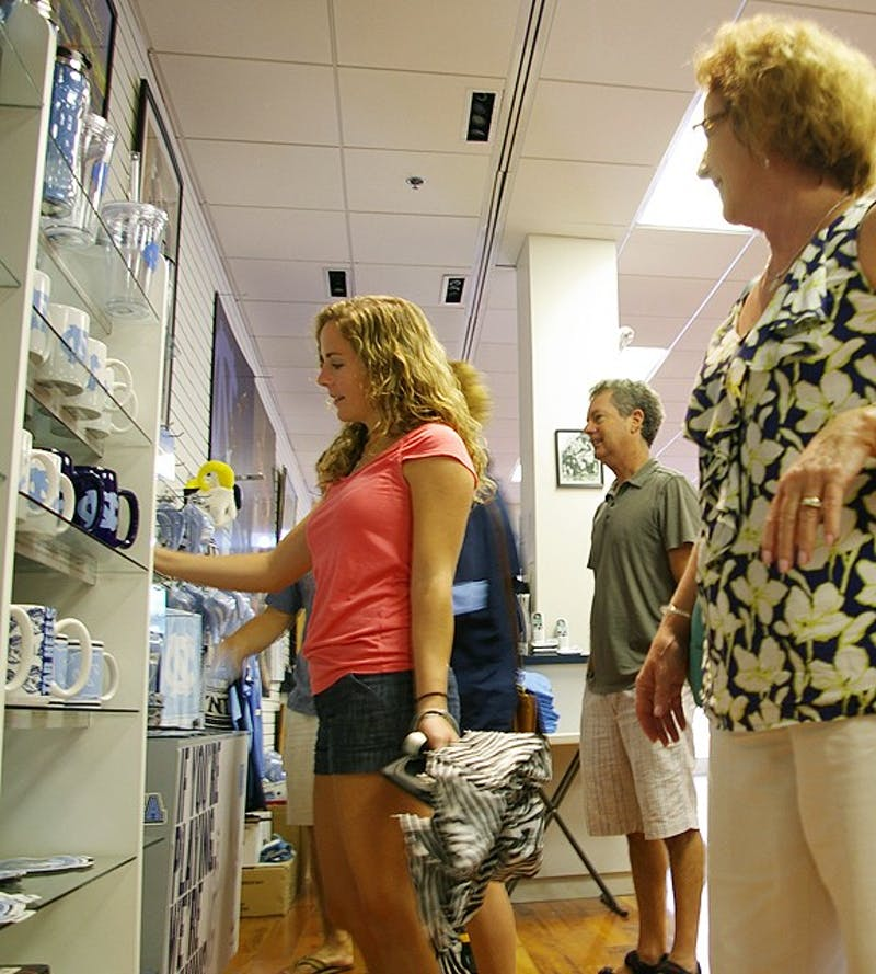 "As the new semester approaches, Chapel Hill has had an increase in tourists visiting and spending their time in stores such as Johnny T-Shirt and Carolina Sportswear. Helen Robertson, sophomore, looks around Carolina Sportswear with her mom, Terry Robertson, and father, David Robertson. The Robertson's were visiting from Morehead City, North Carolina to move Helen into her dorm. Mother Terry Robertson said, ""I love the diversity and all of the opportunities and the fabulous education the school offers."""