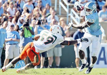 UNC wide receiver Dwight Jones slides past Miami linebacker James Gaines.