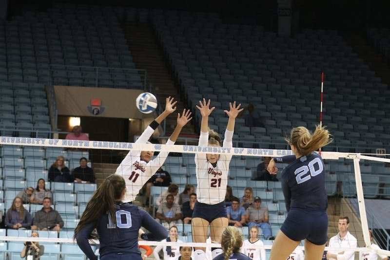 UNC player Ava Bell spikes past UVA defenders on Sunday October 14th in Carmichael Arena.