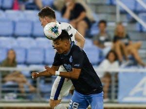 Junior midfielder Raul Aguilera (28) beats Creighton senior midfielder Luke Haakenson (15) to head the ball. UNC and Creighton tied 2-2 in double overtime.