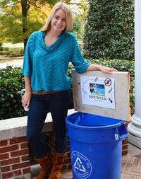 Elly Withers stands with one of the recycling bins she has altered in order to make recycling more fun. She hopes to encourage all of the fraternities on campus to join in with her recycling campaign.