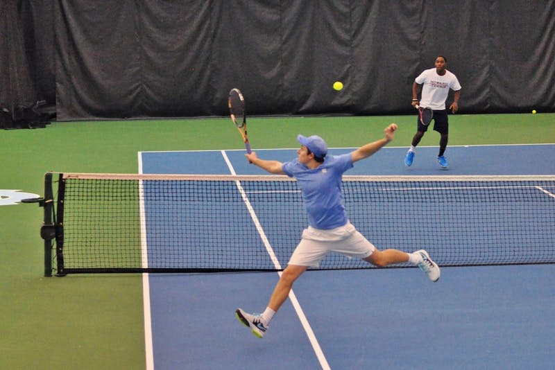 UNC junior Connor Daly reaches for a volley against Howard in a doubles match.