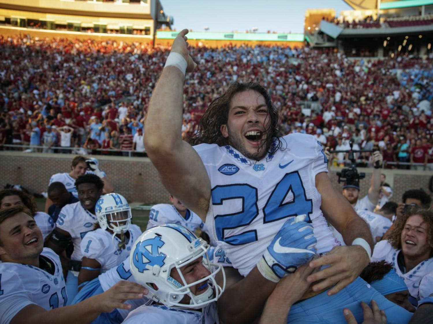 Nick Weiler (24) is hoisted by his teamates after he scored a 54-yard field goal to win the game against FSU.