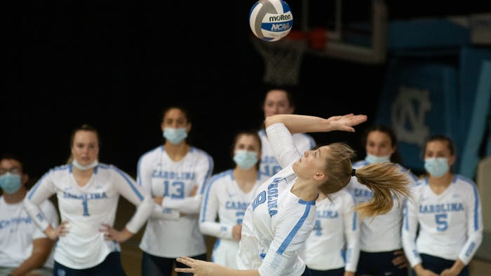 UNC freshman outside hitter Mabrey Shaffmaster serves the ball as her teammates look on during the Tar Heels' home matchup against Elon on Sept. 14, 2021. The Heels won 3-0.