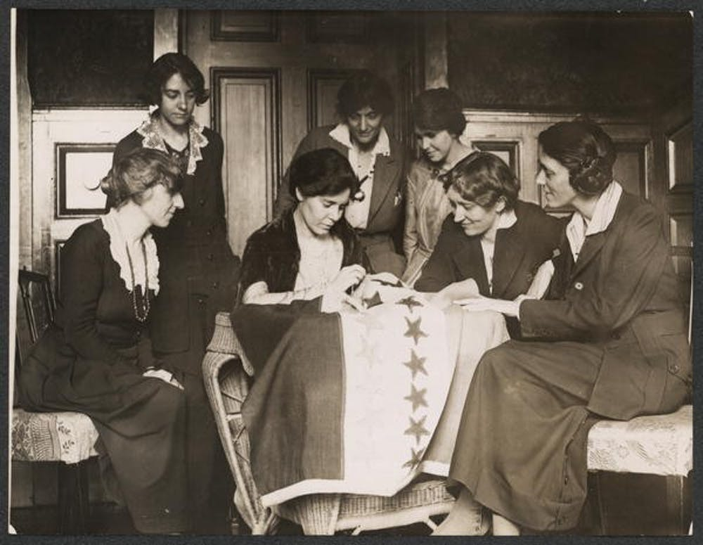 <p>Alice Paul sews a star onto the NWP Ratification Flag, representing another state's ratification of the 19th Amendment. Photo courtesy of The Suffragist Project.</p>