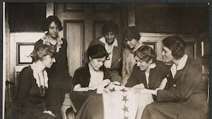 Alice Paul sews a star onto the NWP Ratification Flag, representing another state's ratification of the 19th Amendment. Photo courtesy of The Suffragist Project.