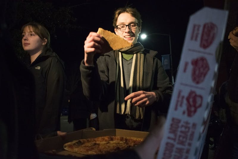 A demonstrator accepts pizza offered by organizers at a gathering to celebrate the removal of Silent Sam's pedestal and plaques in the Peace and Justice Plaza on Tuesday, Jan. 15, 2019.
