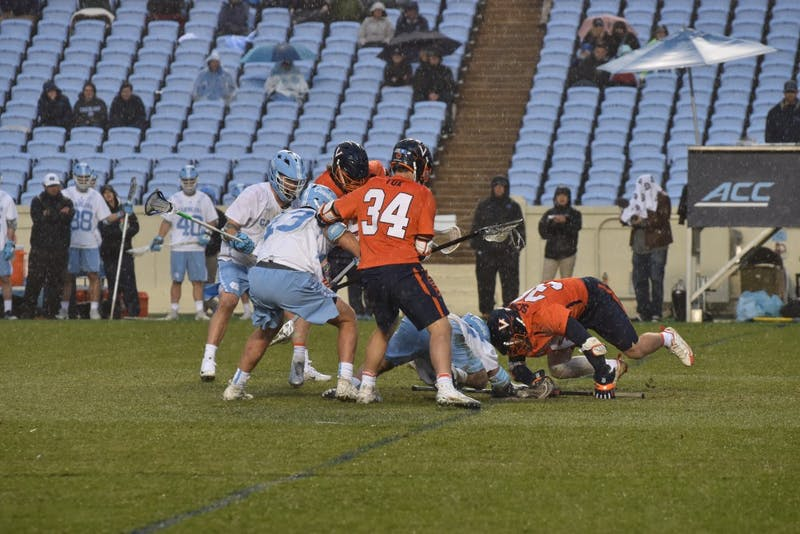 UNC and Virginia players fight for a ground ball on April 7 in Kenan Stadium.
