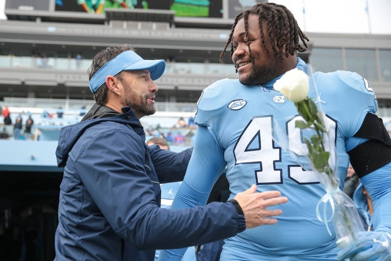 Larry Fedora and Jeremiah Clarke (49) during the senior day ceremony on Saturday, Nov. 24, 2018 in Kenan Memorial Stadium.