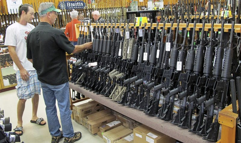 Customers shop for guns at Jim's Pawn Shop in Fayetteville, North Carolina. Josh Hondorp, who manages the pawn business at the store, which also sells guns and features a shooting range, says the federal government shutdown could cut into sales. (David Zucchino/Los Angeles Times/MCT)