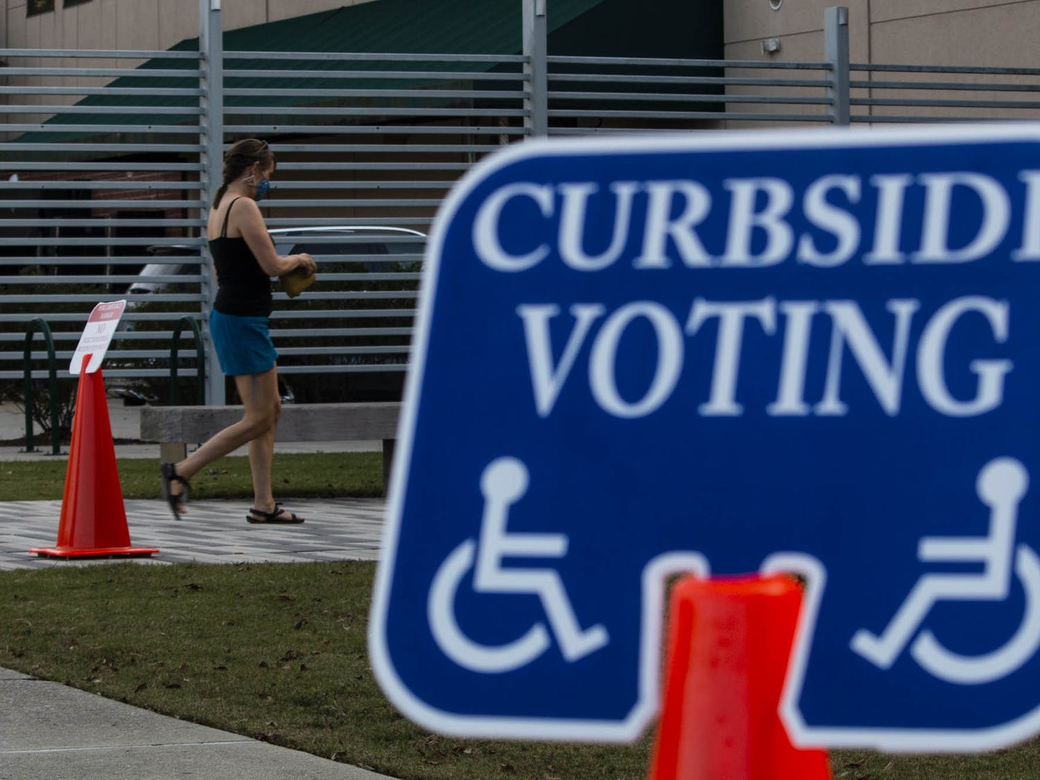 A voter walks towards the early voting site entrance at the University Mall on Thursday, Oct. 22, 2020.