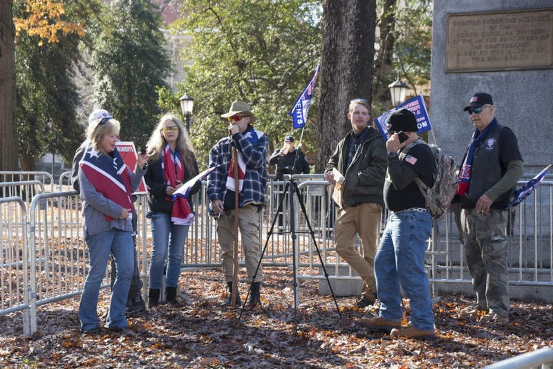 Members of Heirs to the Confederacy stand inside metal gates Sunday afternoon in McCorkle Place. They said a brief prayer before protesting in support of the toppled Silent Sam monument.